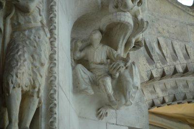 悪魔に爆弾を手渡されてる男の彫刻